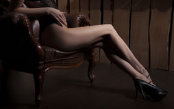Sexy woman in black lingerie, mask and heels on luxury brown leather chair, studio Royalty Free Stock Images