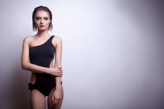 Sexy woman in black swimsuit on grey background Stock Photo