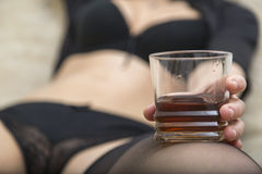 Sexy woman in black underwear holding glass of whiskey Royalty Free Stock Photography