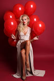 Sexy woman with blond curly hair wears elegant dress, holding a lot of red air balloons Royalty Free Stock Photos
