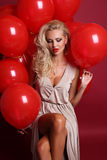 Sexy woman with blond curly hair wears elegant dress, holding a lot of red air balloons Stock Images