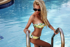 woman with blond hair in bikini and sunglasses posing in swimming pool Royalty Free Stock Photography