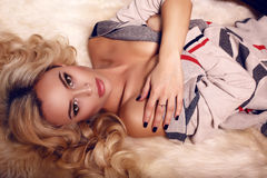 Sexy woman with blond hair in cardigan relaxing on fur carpet Stock Photography
