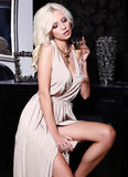 Sexy woman with blond hair celebrating with glass of champagne Royalty Free Stock Photos
