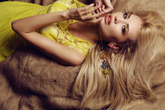 Sexy woman with blond hair in elegant dress with bright makeup. Fashion studio photo of beautiful sexy woman with blond hair in elegant dress with bijou Royalty Free Stock Images