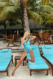Woman with blond hair in elegant swimming suit relaxing on. Fashion outdoor photo of beautiful woman with blond hair in elegant swimming suit relaxing on chaise stock images