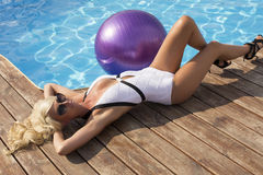 woman with blond hair in elegant swimsuit with sunglasses Stock Photography