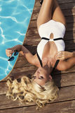 Sexy woman with blond hair in elegant swimsuit with sunglasses Royalty Free Stock Photo