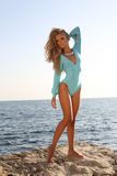 Sexy woman with blond hair in fashion swimsuit posing on beach. Fashion outdoor photo of sexy beautiful woman with long blond hair wearing elegant blue swimsuit Stock Image