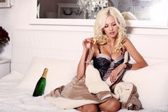 Sexy woman with blond hair in lingerie with glass of champagne Stock Images