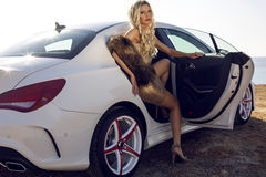Sexy woman with blond hair posing in luxurious white car. Fashion outdoor photo of sexy beautiful woman with long blond hair in elegant dress and fur posing in Stock Images