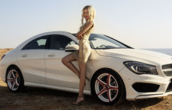 Sexy woman with blond hair posing beside a luxury auto Royalty Free Stock Images