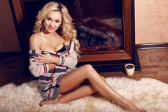 Sexy woman with blond hair relaxing beside a chimney at bedroom Royalty Free Stock Photos