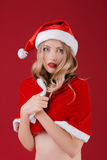 Sexy woman blonde in the clothes of Santa Claus. Portrait of sexy woman blonde in the clothes of Santa Claus  froze on a red background Stock Photo