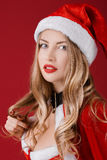 Sexy woman blonde in the clothes of Santa Claus. Portrait of sexy woman blonde in the clothes of Santa Claus on a red background Royalty Free Stock Photography