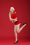 Sexy woman blonde in the clothes of Santa Claus. On a red background Royalty Free Stock Image