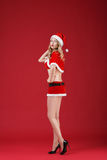 Sexy woman blonde in the clothes of Santa Claus. On a red background Stock Photos