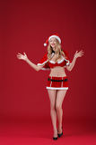 Sexy woman blonde in the clothes of Santa Claus. Sexy smiling woman blonde in the clothes of Santa Claus on a red background Royalty Free Stock Photo