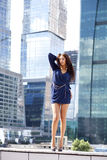 Sexy woman in a blue dress is stretching near skyscrapers Royalty Free Stock Images