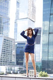 Sexy woman in a blue dress is stretching near skyscrapers Royalty Free Stock Photos