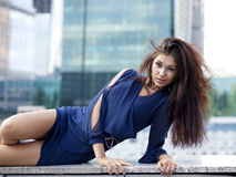 Sexy woman in a blue dress is stretching near skyscrapers Stock Photography