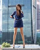 Sexy woman in a blue dress is stretching near skyscrapers Royalty Free Stock Photography
