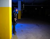 Sexy woman with blue hair holding two guns and looking as killer in underground parking Stock Image