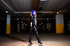 Sexy woman with blue hair holding two guns and looking as killer in underground parking Stock Photo