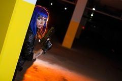 Sexy woman with blue hair holding two guns and looking as killer in underground parking Royalty Free Stock Photography