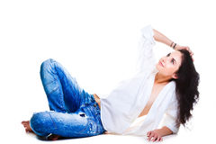 Sexy woman in blue jeans lying on white floor Stock Image