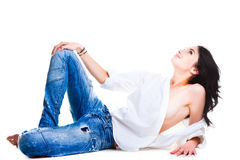 Sexy woman in blue jeans lying on white floor Stock Photos
