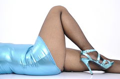 Sexy woman blue shiny stretchy mini dress lies on her back Stock Photography
