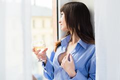 Sexy woman in blue shirt looking through the window Royalty Free Stock Photo