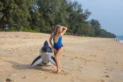 Woman in blue swimsuit on the beach with inflatable toy. Woman is standing on the beach in blue swimsuit with inflatable toy killer whale in her hands, Mai Khao stock photo