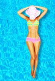 Sexy woman body in the pool. Sexy woman body in pool, female relaxing in water, girl lying down and tanning, luxury lady in bikini over blue background, slim fit Stock Photo