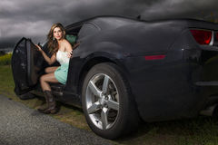 Sexy woman in boots getting out of car Stock Image