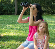 Sexy woman and bored girl with black binoculars. Mother and her daughter looking through binoculars in the park Royalty Free Stock Image