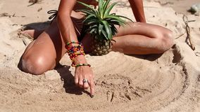 Sexy woman in a brown swimsuit on the beach with pineapple drawing on sand. Young female enjoying summer vacation on a stock footage