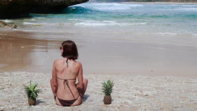 Sexy woman in a brown swimsuit on the beach with pineapple. Young female enjoying summer vacation on a tropical Bali stock video footage
