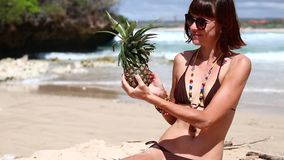 Sexy woman in a brown swimsuit on the beach with pineapple. Young female enjoying summer vacation on a tropical Bali stock video