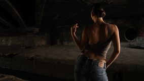 Sexy woman with brown top and jeans dancing in the dark stock footage