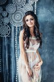 Woman Brunette in White Bridal Lingerie Dress Posing. On Vintage Background royalty free stock images