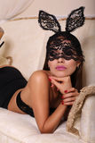 Sexy woman in bunny's mask lying on the divan Stock Photos