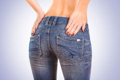 Sexy woman buttocks in blue jeans on the blue Royalty Free Stock Photography