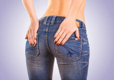 Sexy woman buttocks in blue jeans on the blue Royalty Free Stock Photo