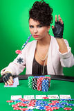 Sexy woman calls poker bet. Sexy young lady throwing some chips at the poker table, raising or calling you, looking at the camera with a poker face. on green Stock Images