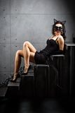 Sexy woman in catwoman suit lying on stairs Royalty Free Stock Photos