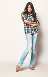 Sexy woman in check shirt and blue jeans. In studio Stock Images