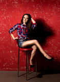 Sexy woman in checkered shirt and shorts posing on high chair Royalty Free Stock Photography