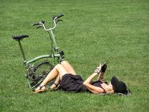 Sexy woman chilling on grass. Sexy woman chilling on the grass laying on her back in Central Park New York City NYC with a folded bike at her feet Stock Photos
